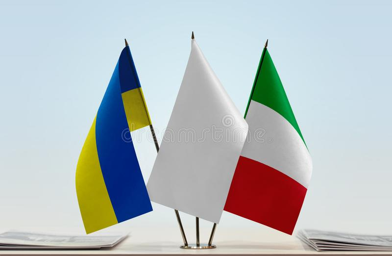 Flags of Ukraine and Italy. Desktop flags of Ukraine and Italy with a white flag in the middle stock photo