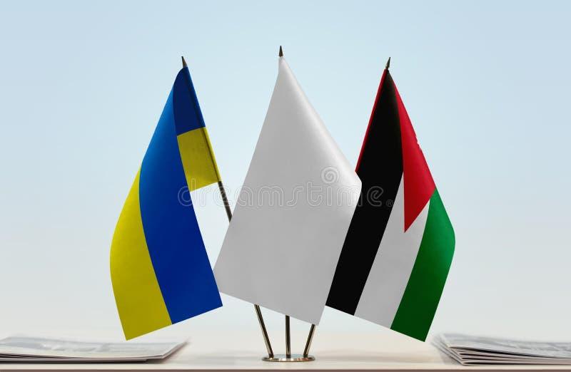 Flags of Ukraine and Jordan. Desktop flags of Ukraine and Jordan with white flag between royalty free stock photo