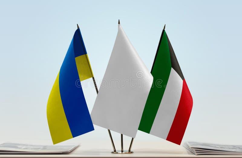 Flags of Ukraine and Kuwait. Desktop flags of Ukraine and Kuwait with white flag between stock photography