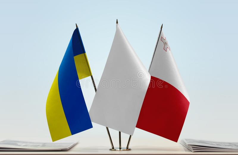 Flags of Ukraine and Malta. Desktop flags of Ukraine and Malta with a white flag in the middle stock photography