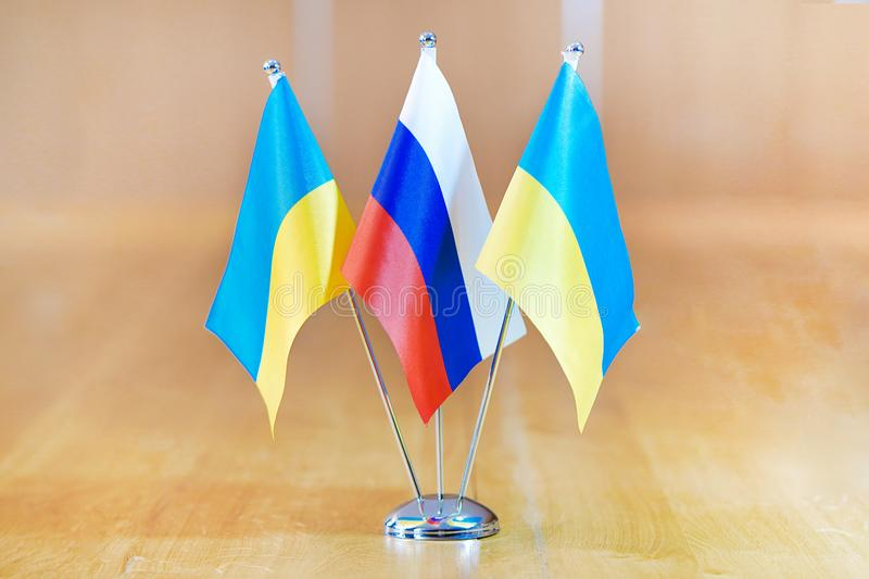 Flags of Ukraine and Russia. Three flags on the table. Flags of Ukraine and Russia. Flags of Ukraine and Russia on the table during a meeting of foreign royalty free stock photos