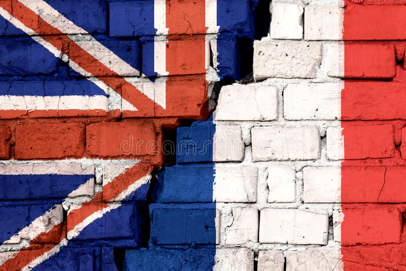 Flags of United Kingdom and France on the brick wall with big crack in the middle. Symbol of problems between countries.  stock illustration