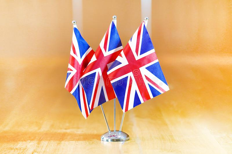 Flags of United Kingdom. Three flags on the table. Flags of United Kingdom. Flags of United Kingdom on the table during a meeting of foreign ministers of UK stock image