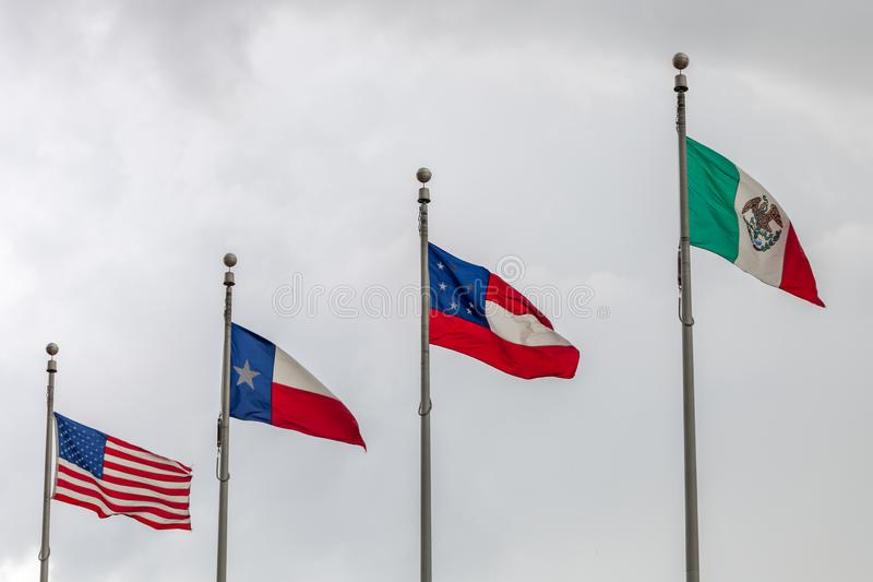 Flags of the Untied States of America, the state of Texas, the first official national flag of the Confederacy and of Mexico again. St a cloudy sky royalty free stock images