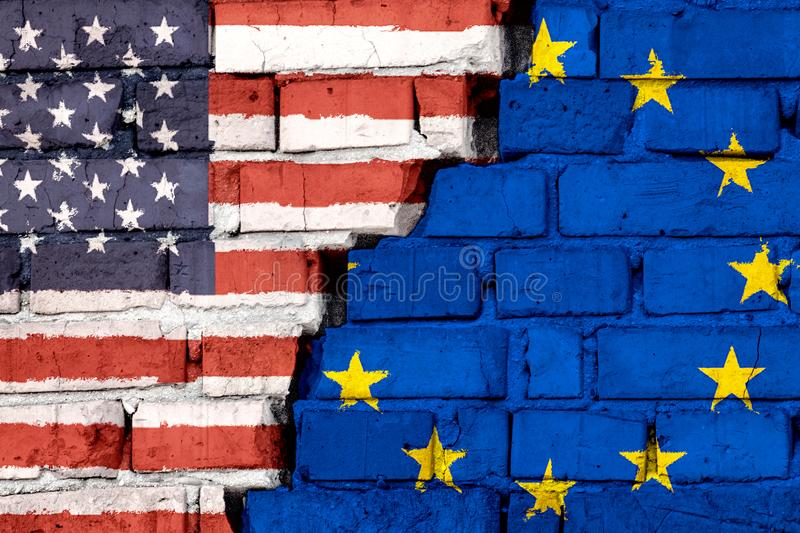 Flags of USA and European Union EU on the brick wall with big crack in the middle. Symbol of problems between countries royalty free stock photo