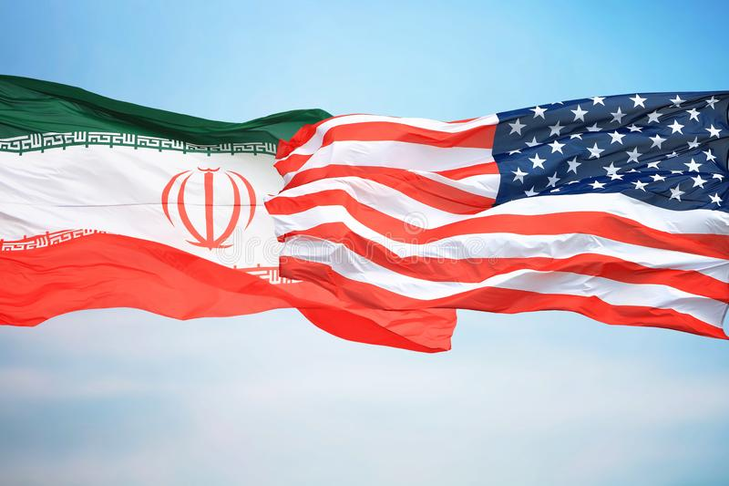 Flags of the USA and Iran. Against the background of the blue sky stock images