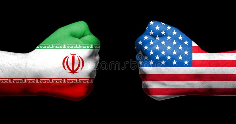 Flags of USA and Iran painted on two clenched fists facing each. Other on black background/Tensed relationship between USA and Iran concept stock photography