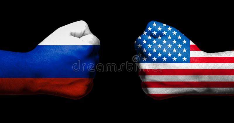 Flags of USA and Russia painted on two clenched fists facing each other on black background/Tensed relationship between USA and Ru royalty free stock image
