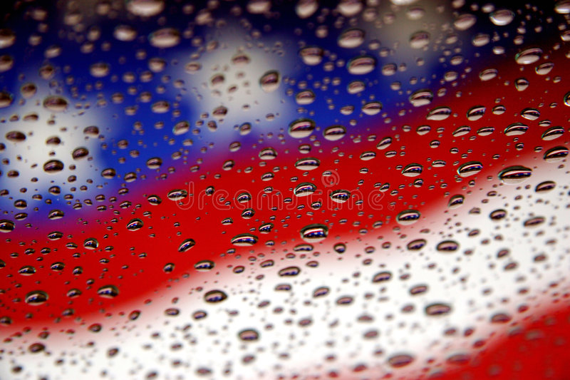 Flags and water drops. American flag in background with rain drops on window and reflections stock photo