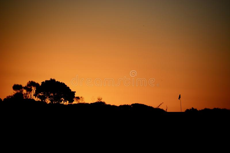 A Flagstick at a Golf Course; beautiful sunset colours and a silhouette of the golf flagstick against the evening sky. stock photography
