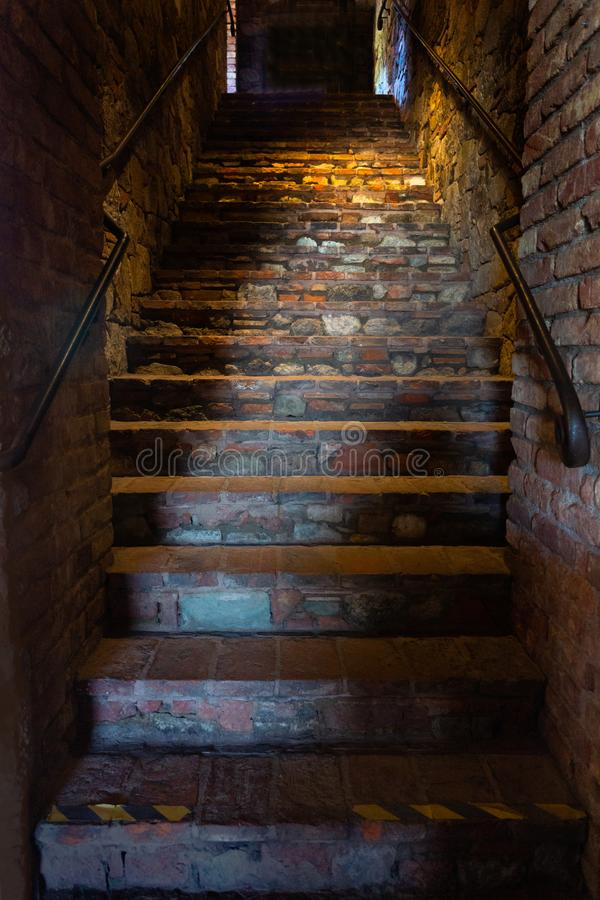 Stone Stairwell in Medieval Castle. Flagstone stairwell in shadows with ambient lighting. Rustic setting of old castle. Spooky lighting stock photos