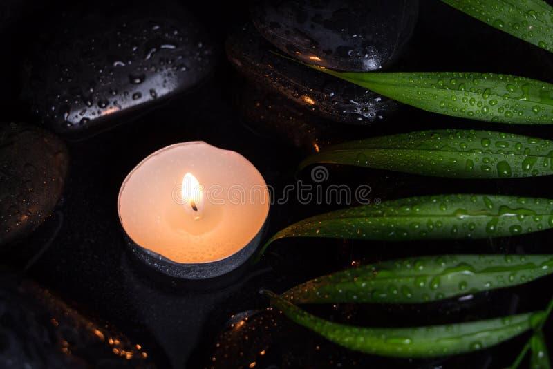Flairez la bougie allumée sur les pierres humides noires et la feuille verte avec des gouttelettes, photographie foncée photos libres de droits