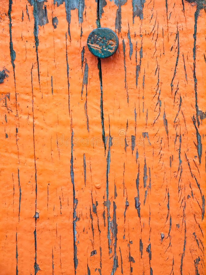 Flaking paint on aged wood with iron nail with letters NAP. Closeup of aging wooden beach marker post showing weathered orange paint and head of nail carrying royalty free stock images