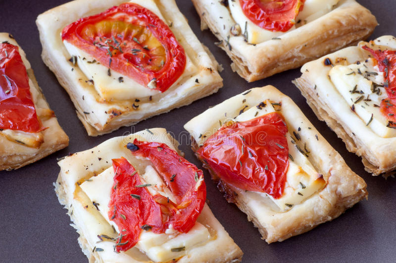 Flaky pastry snack with feta and tomatoes royalty free stock photography