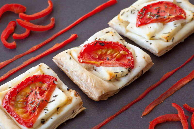 Flaky pastry snack with feta and tomatoes royalty free stock image
