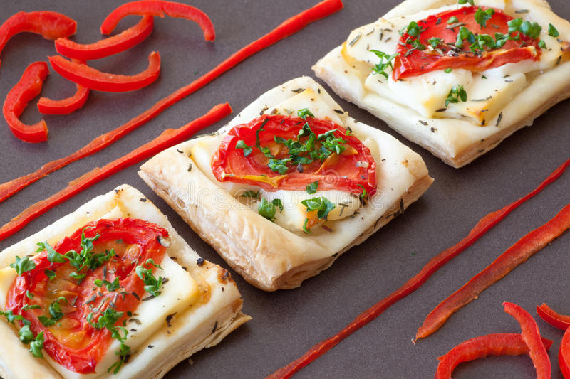 Flaky pastry snack with feta, tomatoes and herbs royalty free stock image