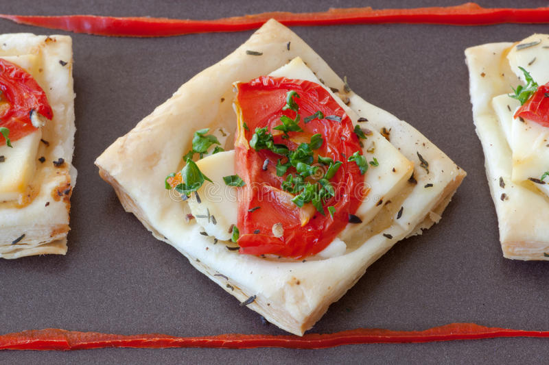 Flaky pastry snack with feta, tomatoes and herbs royalty free stock images
