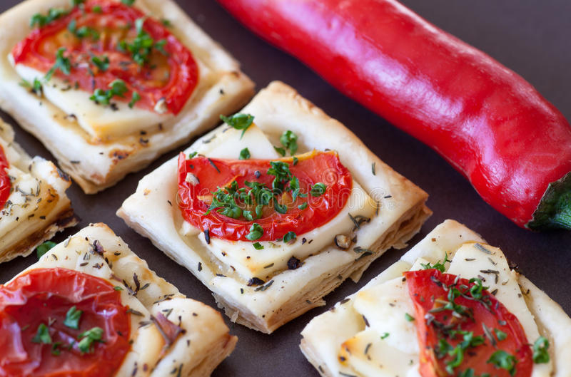 Flaky pastry snack with feta, tomatoes and herbs stock images