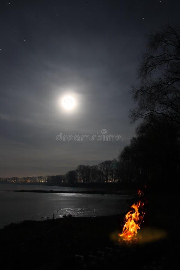 Flama e lua da fogueira sobre o lago fotos de stock