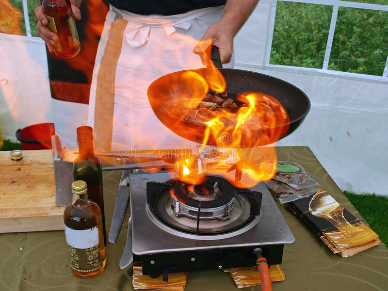Flambe cook in flames. Chef in a restaurant cooks in flambe flames royalty free stock photo