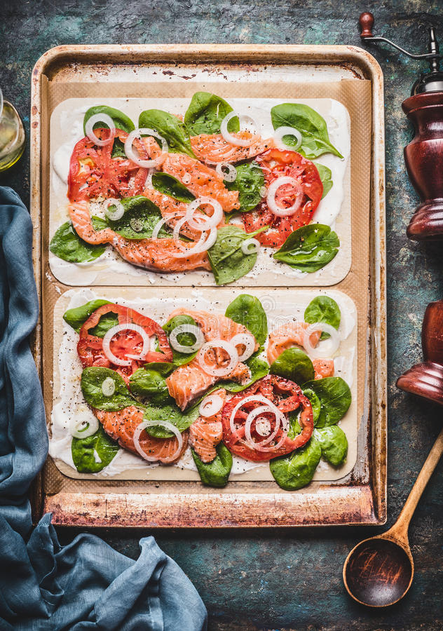 Flambee de Tarte con los salmones, espinaca y tomates, cocinando la preparación en fondo rústico de la tabla de cocina fotos de archivo