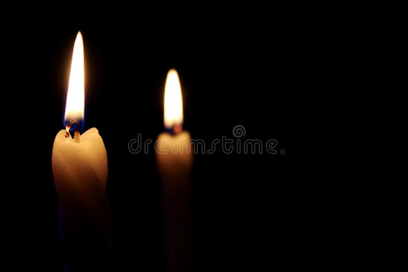 A candle burns in the dark stock photography