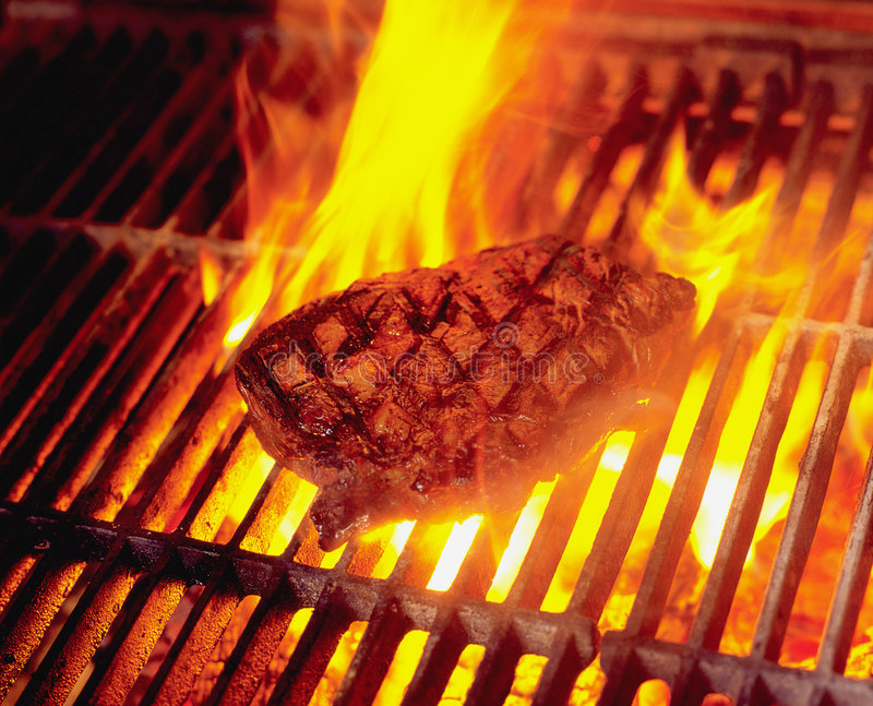 Flame Grill. Steak cooking on wood fired flame grill in Restaurant stock image
