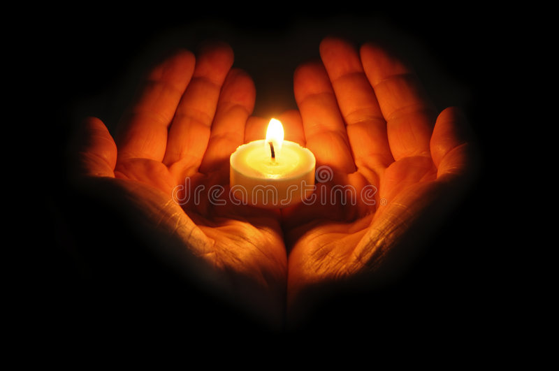 Flame is in hands. Hands carry a burning candle