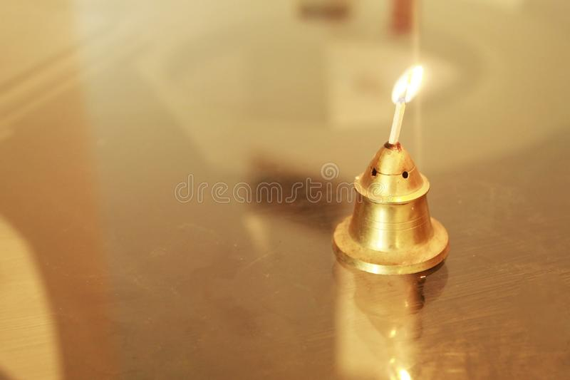 Flame of a lit matchstick inserted in an incense stand and placed on top of a glass table stock images