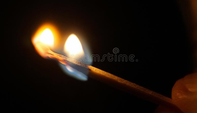 Flame of the match burning in fingers. In the dark stock photos