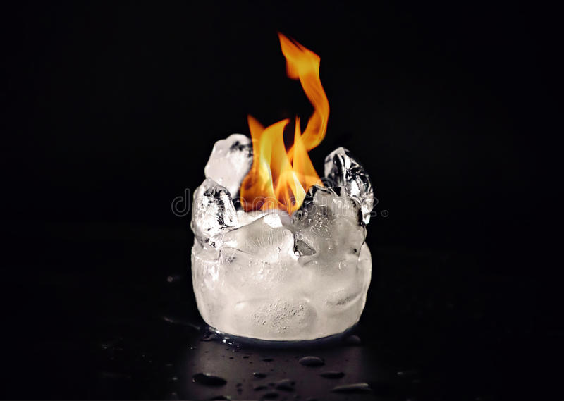 Flame melting ice. Flame melting a piece of ice on a black background royalty free stock images
