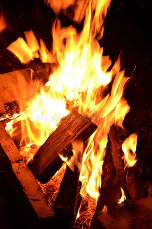 Flame in the night. In the fire, we can see recently tossed firewood royalty free stock photo