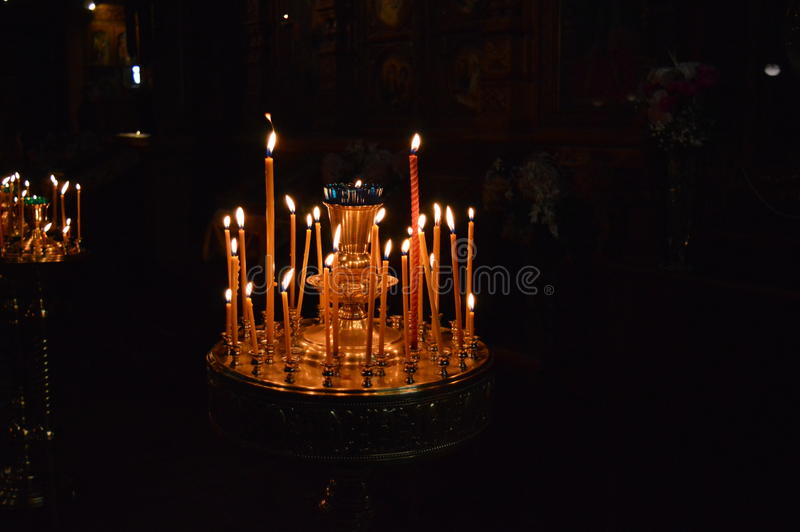 Flame of wax candles in the church stock image