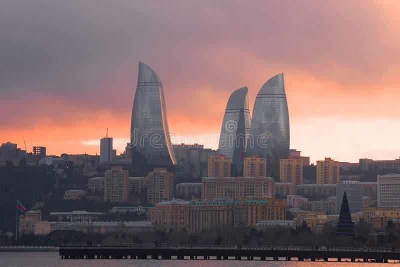 Flamee las torres en el paisaje de la ciudad en puesta del sol Baku, Azerbaijan imagen de archivo