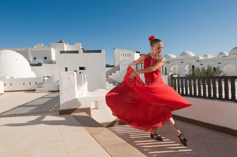 Flamenco dancer. Attractive flamenco dancer wearing traditional red dress with flower in her hair royalty free stock photography