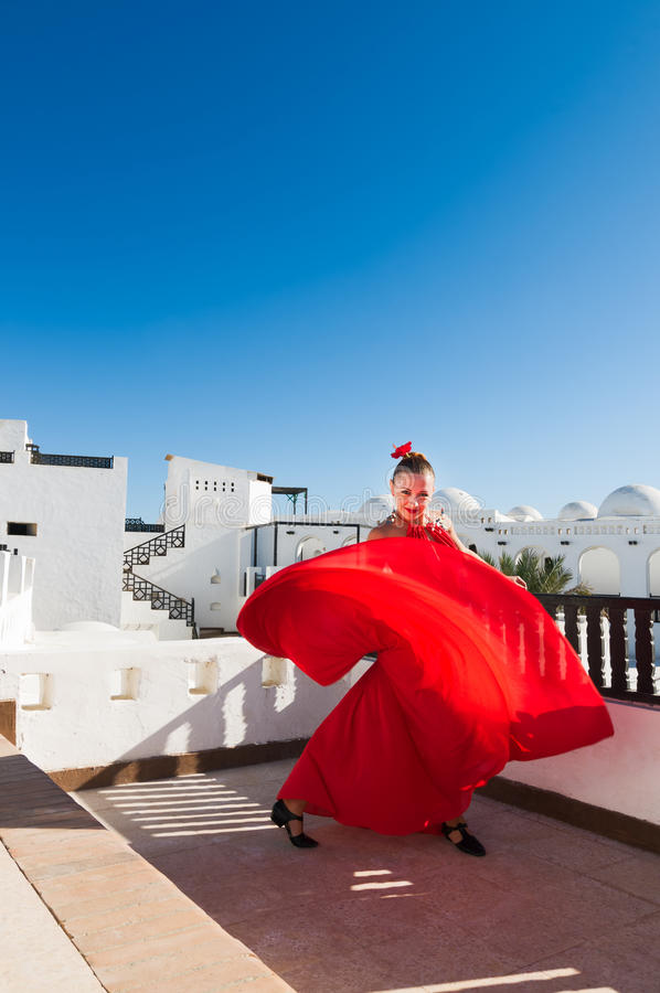 Flamenco dancer. Attractive flamenco dancer wearing traditional red dress with flower in her hair royalty free stock image