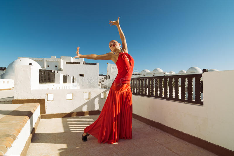 Flamenco dancer. Attractive flamenco dancer wearing traditional red dress with flower in her hair royalty free stock photo