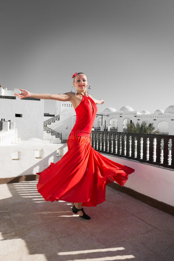 Flamenco dancer. Attractive flamenco dancer wearing traditional red dress with flower in her hair stock images