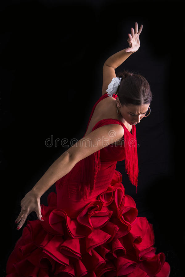 Flamenco dancer dressed in red with an expression. Of feeling passionate in black background royalty free stock photo