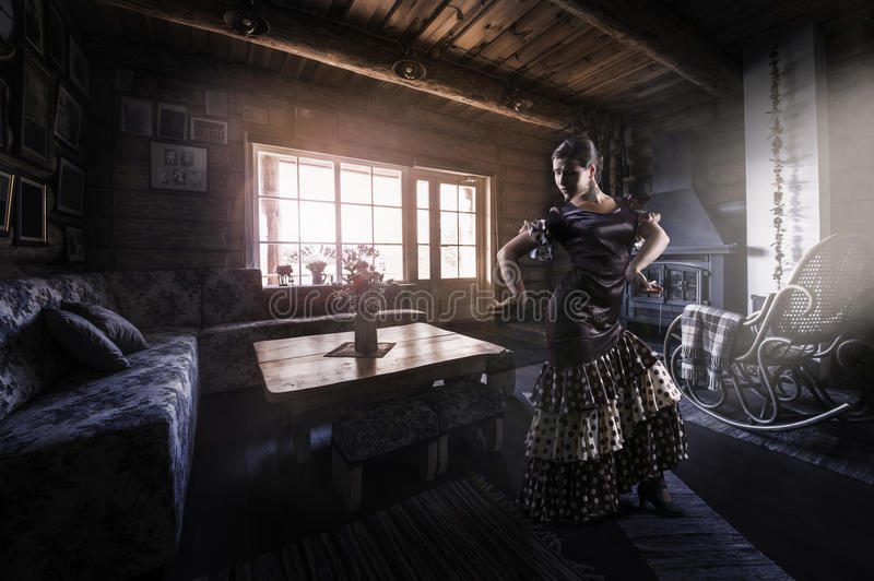 Flamenco dancer silhoutte indoors, rural interior. Beautiful woman-spanish flamenco dancer, wearing brown color silk dress with polka dots, dancing indoors. Over stock images