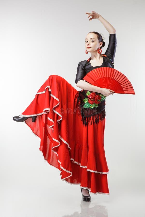 Flamenco de danse de jeune femme dans la robe rouge sur le blanc photographie stock