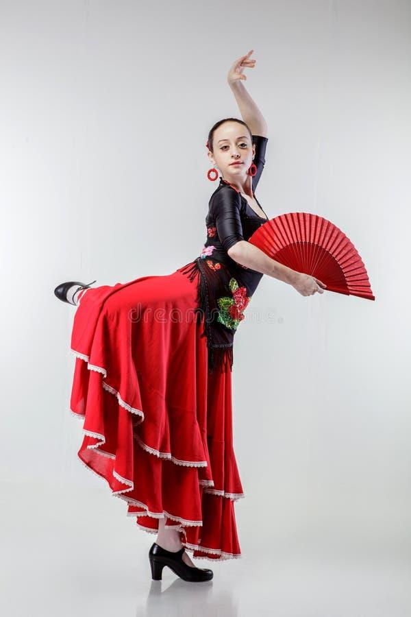 Flamenco de danse de jeune femme dans la robe rouge sur le blanc image stock