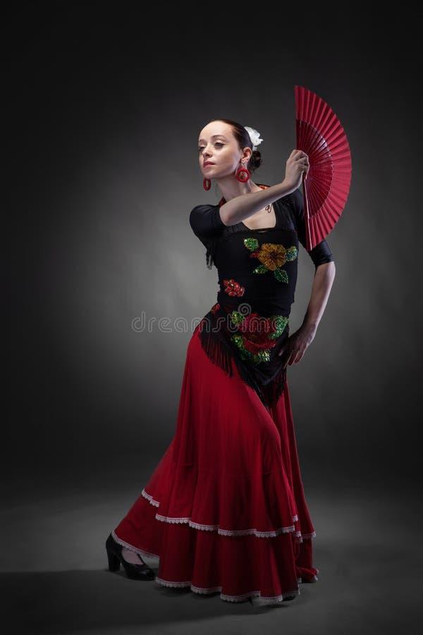 Flamenco di dancing della giovane donna con il fan sul nero immagine stock libera da diritti