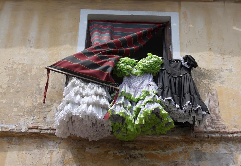 Flamenco dresses hanging out of window. Flamenco dresses in green, black and white hanging out a window in andalusia spain stock images