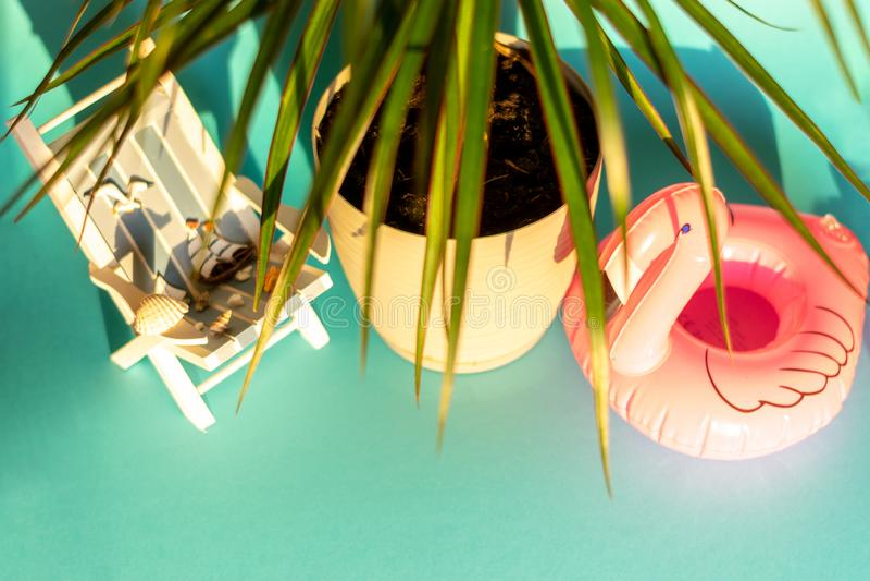 Flamenco y deckchair inflables en un fondo azul, partido del flotador de la piscina, foto de archivo libre de regalías