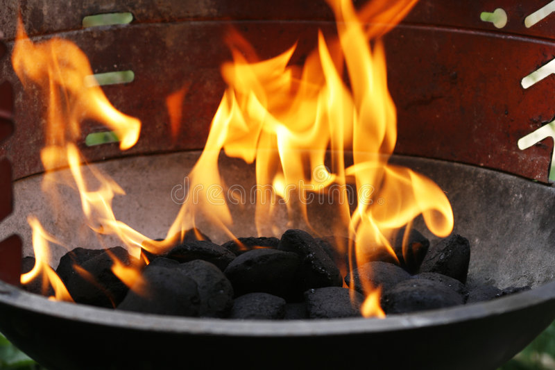 Flames in barbecue. Barbecue charcoal with big golden flames royalty free stock images