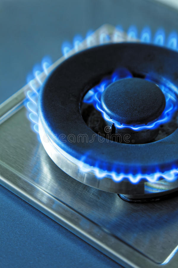 Flames of blue gas. Close up burning fire ring from a kitchen gas stove. Tinted photo.  royalty free stock photography