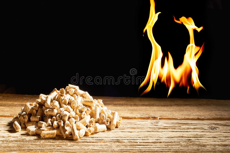 Flames burning behind a heap of wood pellets. Flames burning in the darkness behind a heap of wood pellets on a rustic table in a concept of natural renewable stock photo