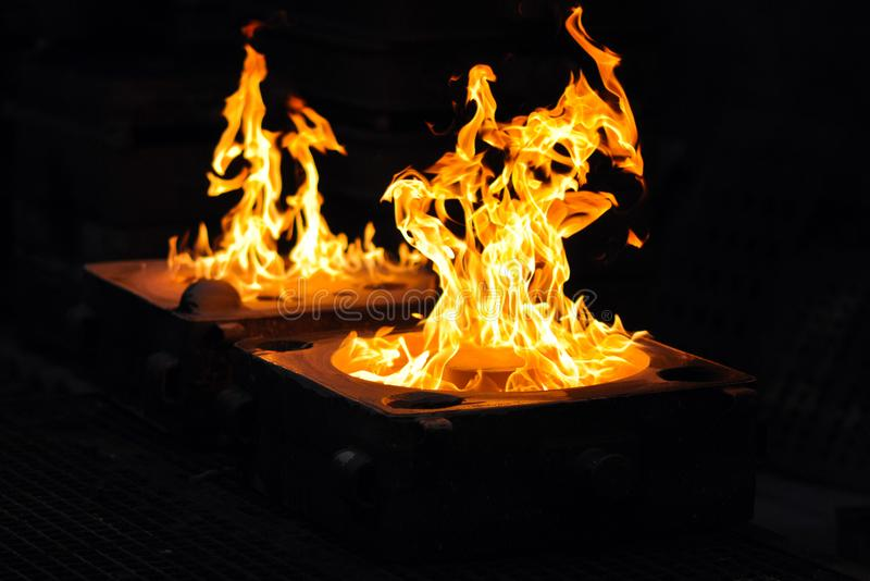 Flames after casting a workpiece in a foundry - production of s. Teel castings in an industrial company stock image