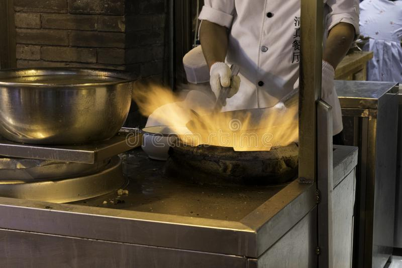 Fire and Food  a chinese chef prepares food in a wok stock photography